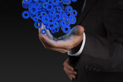 Businessman hand showing gears cogs Stock Image