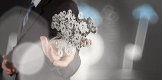 Businessman hand showing gears cogs to success Stock Image