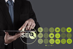 Businessman hand showing search engine optimization SEO Stock Images