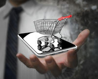 Businessman hand showing shopping cart with smart phone Stock Images