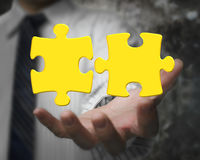 Businessman hand showing two 3D gold jigsaw puzzle pieces Stock Photo