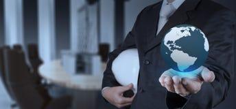 Businessman hand shows the earth as construction concept Stock Photos