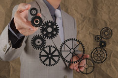 Businessman hand shows gear to success concept Royalty Free Stock Images