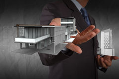 Businessman hand shows house model with crumpled paper backgroun Stock Photography