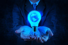 Businessman hand shows Light bulb with planet Earth Stock Photography