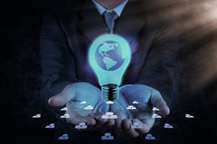 Businessman hand shows Light bulb with planet Earth Stock Photo