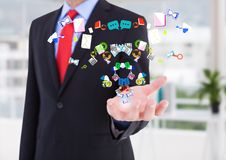 Businessman hand spread of with application icons coming up from it in the office ( blurred) Royalty Free Stock Images