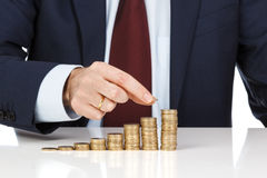 Businessman hand stacking one euro coins into increasing columns Royalty Free Stock Images