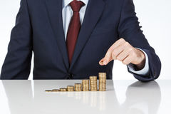Businessman hand stacking one euro coins into increasing columns. Financial concept. Closeup Royalty Free Stock Photo