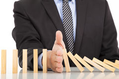 Businessman hand stop dominoes continuous toppled royalty free stock photo