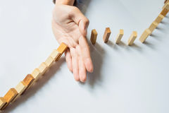 Businessman hand stop dominoes continuous toppled or risk with c Royalty Free Stock Photography