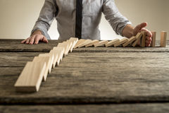 Businessman hand stopping domino effect. Rough wooden table with copy space Royalty Free Stock Photo