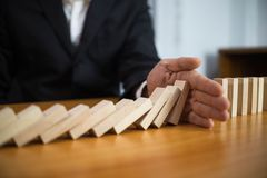 Businessman hand stops domino continuous overturned meaning that hindered business failure. Stop over this business failure. Concept royalty free stock photos