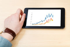 Businessman hand and tablet PC with business graph. On screen at office desk Stock Photos