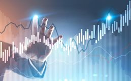 Businessman hand touching a graph hologram. Hand of a businessman interacting with glowing growing graphs against a blurred blue background. Concept of trading Stock Photo