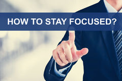 Businessman hand touching HOW TO STAY FOCUSED? message on virtua. L screen royalty free stock photography