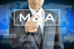 Businessman hand touching M & A on virtual screen stock photos