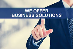 Businessman hand touching WE OFFER BUSINESS SOLUTIONS tab on vir Stock Photo