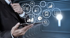 Businessman hand use smart phone computer with email icon as con. Business data analytics management with connected gear cogs with KPI financial charts and graph Royalty Free Stock Images
