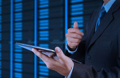 Businessman hand using tablet computer and server room. Background Royalty Free Stock Photography