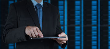 Businessman hand using tablet computer and server room. Background Stock Images
