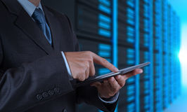 Businessman hand using tablet computer and server room. Background Stock Photo
