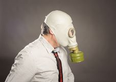 Businessman hand wearing a gas mask. On a gray background Stock Photo