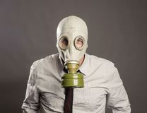 Businessman hand wearing a gas mask. On a gray background Royalty Free Stock Photography