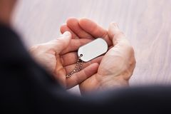 Businessman hand on wooden table holding dog tag Stock Image