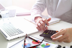 Businessman hand working with finances about cost and calculater. Businessman hand working with finances about cost and calculator and latop with mobile phone on Stock Photography