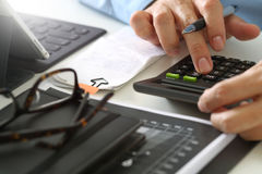 Businessman hand working with finances about cost and calculator. Close up of businessman hand working with finances about cost and calculator and latop with Royalty Free Stock Photography