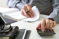 Businessman hand working with finances about cost and calculator Royalty Free Stock Photography