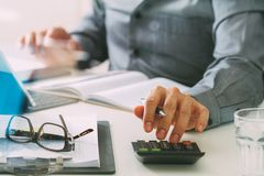 Businessman hand working with finances about cost and calculator Stock Images