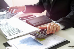 Businessman hand working with finances about cost and calculator. And latop with mobile phone on withe desk in modern office Royalty Free Stock Photo