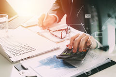 Businessman hand working with finances about cost and calculator. And latop with mobile phone on withe desk in modern office with VR icon diagram Stock Photography
