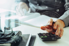 Businessman hand working with finances about cost and calculator. And latop with mobile phone on withe desk in modern office with VR icon diagram Stock Photo