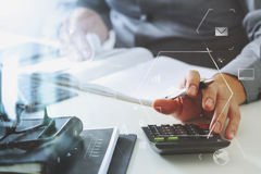 Businessman hand working with finances about cost and calculator. And latop with mobile phone on withe desk in modern office with VR icon diagram Royalty Free Stock Images