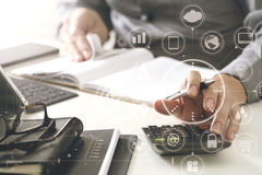 Businessman hand working with finances about cost and calculator. And latop with mobile phone on withe desk in modern office with VR icon diagram Stock Photos