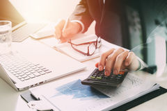 Businessman hand working with finances about cost and calculator. And latop with mobile phone on withe desk in modern office Royalty Free Stock Images