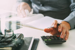 Businessman hand working with finances about cost and calculator. And latop with mobile phone on withe desk in modern office Stock Photo