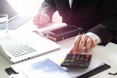 Businessman hand working with finances about cost and calculator. And latop with mobile phone on withe desk in modern office Stock Photos