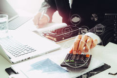 Businessman hand working with finances about cost and calculator. And latop with mobile phone on withe desk in modern office with VR icon diagram Royalty Free Stock Photos