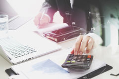 Businessman hand working with finances about cost and calculator. And latop with mobile phone on withe desk in modern office with VR icon diagram Royalty Free Stock Image