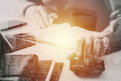 Businessman hand working with finances about cost and calculator. And latop with mobile phone on withe desk in modern office with buildings exposure Stock Photo