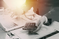 Businessman hand working with finances about cost and calculator. And latop with mobile phone on withe desk in modern office with city exposure Royalty Free Stock Photo