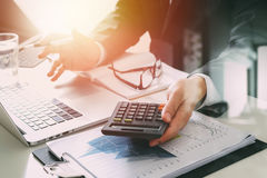 Businessman hand working with finances about cost and calculator. And latop with mobile phone on withe desk in modern office Royalty Free Stock Photos