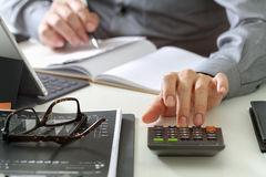 Businessman hand working with finances about cost and calculator. And latop with mobile phone on withe desk in modern office Stock Images