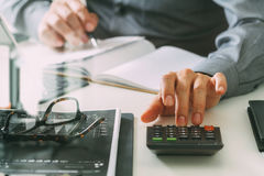 Businessman hand working with finances about cost and calculator. And latop with mobile phone on withe desk in modern office Stock Photography