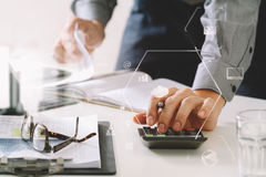 Businessman hand working with finances about cost and calculator. And latop with mobile phone on withe desk in modern office with VR icon diagram Stock Image