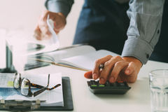 Businessman hand working with finances about cost and calculator. And latop with mobile phone on withe desk in modern office Royalty Free Stock Image